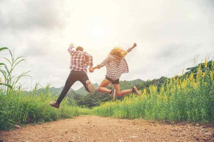 カップルが草原で手をつないでジャンプしている