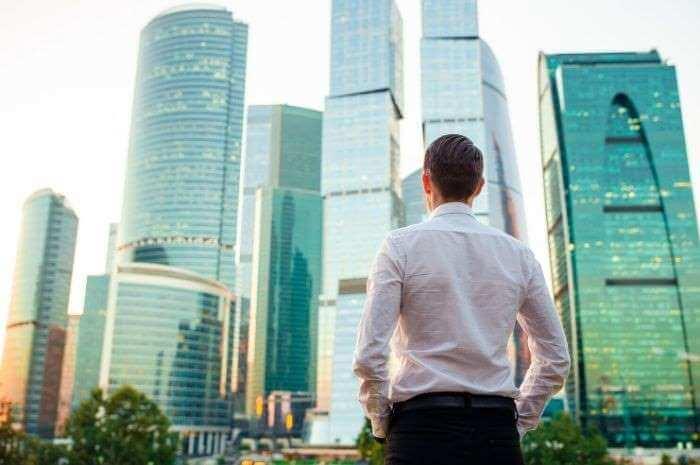 高層ビルを眺めている白シャツの男性