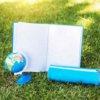 草原にノートと筆箱と地球儀が置かれている