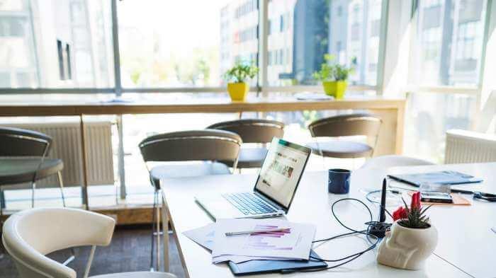 キレイなオフィスのデスクの上にノートパソコンや筆記用具がおかれている