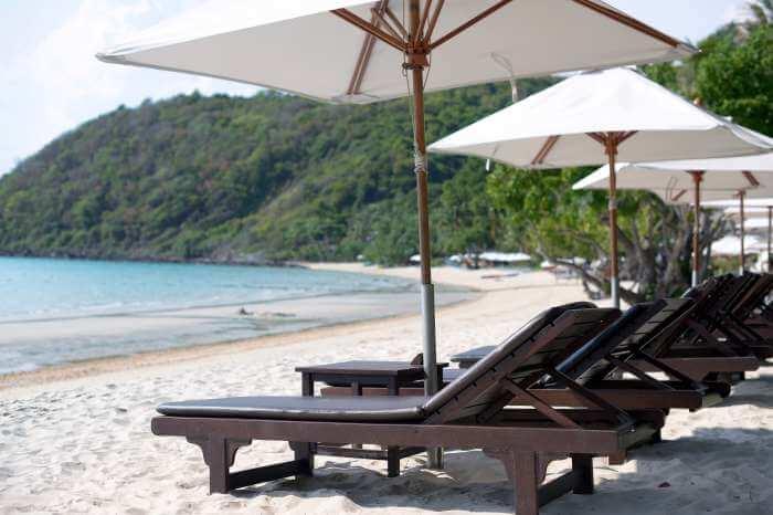 真夏のビーチにパラソルと椅子が並んでいる