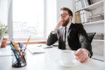 会社のデスクであくびをしているスーツ姿の男性