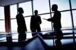 スーツ姿の男性三人が会議室で会議を行っている
