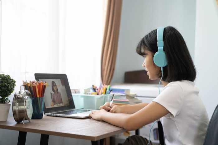 ノートパソコンでオンライン学習をしている少女