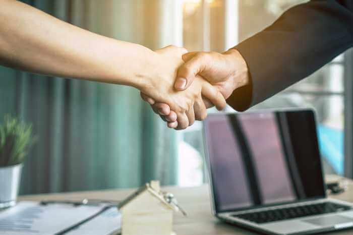 オフィスで握手をする二人のビジネスマンの手