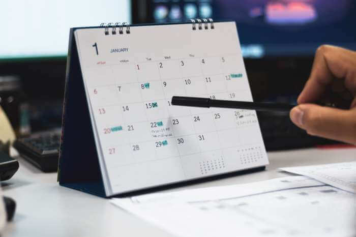 カレンダーをペンで差して考える男性