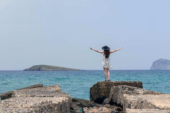 海の岩場で両手を広げて立っている女性