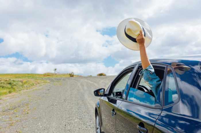 車の後部座席の窓から帽子を持って手をふっている