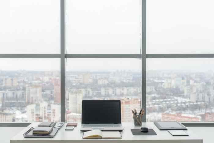 高層階の綺麗な景色の窓の前のデスクにパソコンと筆記用具