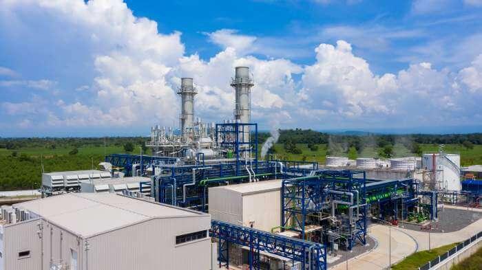 工場の煙突から綺麗な青空に煙が出ている