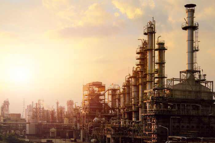 石油化学工場が夕焼けの空に照らされている