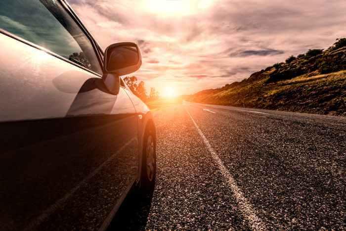 道路を走っている自動車を夕日が照らしている