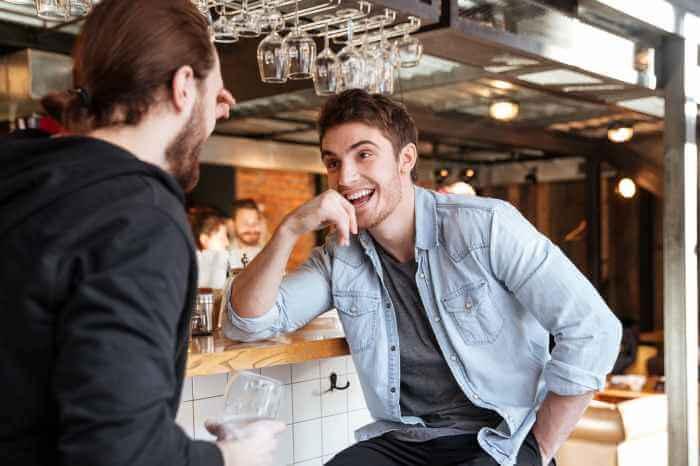 バーで楽しそうに友人と話している男性
