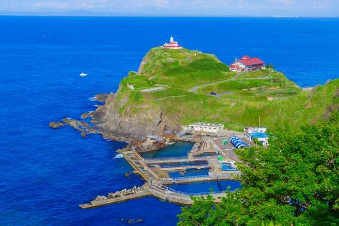 高い山から見た岸辺にある灯台とその周辺の景色