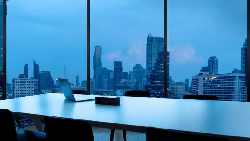 日が沈みかけた時間帯の会議室と窓の外の風景