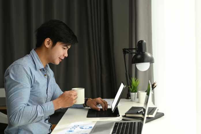 家のデスクでコーヒーを飲みながらパソコンをいじっている男性