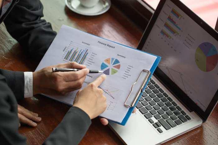 グラフ紙に表示された財務統計を分析する2人のスーツの男性