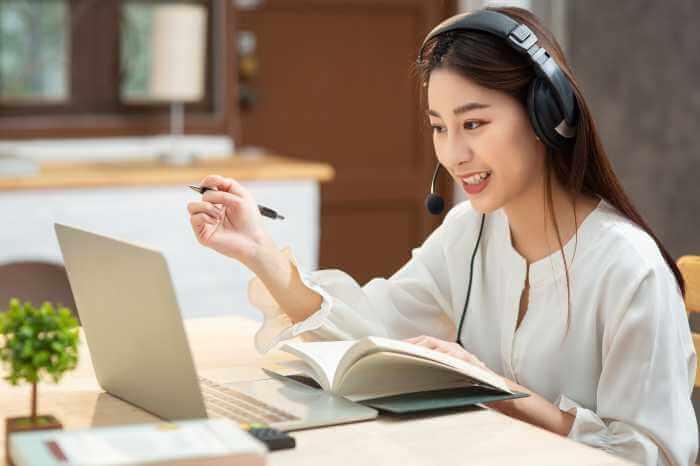 ヘッドホンをしてパソコンでオンラインレッスンを受けている若い女性