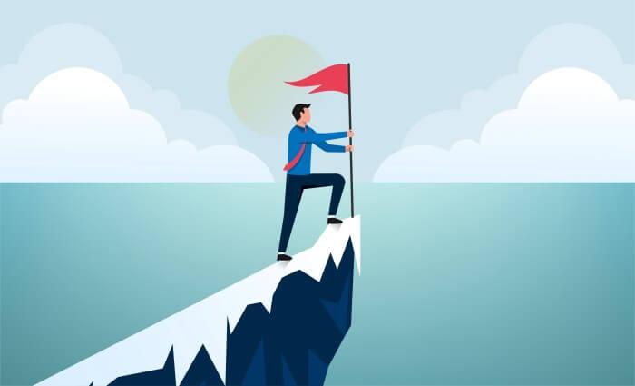 退職することに成功して海辺の崖に旗を立てるビジネスマン