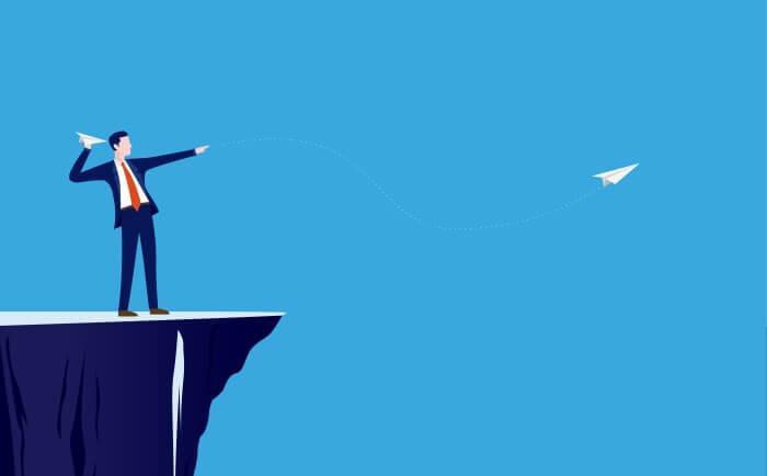高い崖から空に向かって紙飛行機を飛ばしているビジネスマン