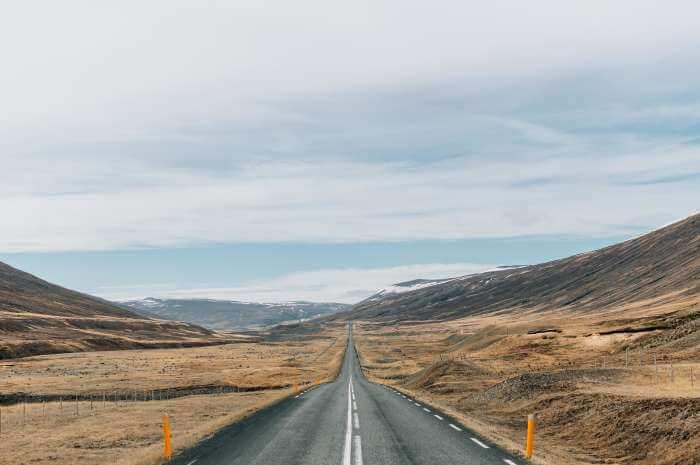 アイスランドの山の風景と地平線のように続く道路