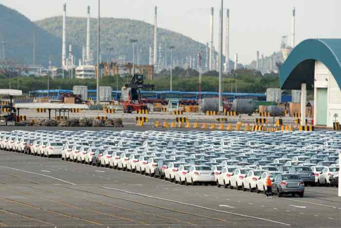 自動車の新品の完成車が工場の広い敷地に数百台並べて置かれている