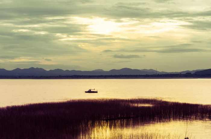 陽が沈んできた湖にボートが浮いている