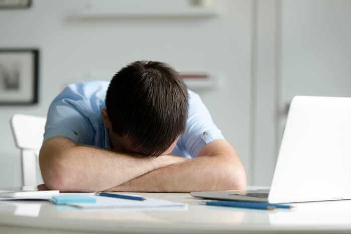 デスクのパソコンの前で居眠りしている男性